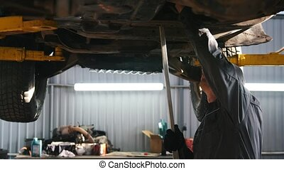 Mechanic in car service checks the auto's bottom for luxury...