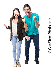 Excited young couple celebrating - Full length portrait of a...