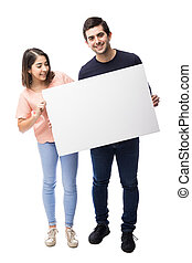Cute couple holding a white sign