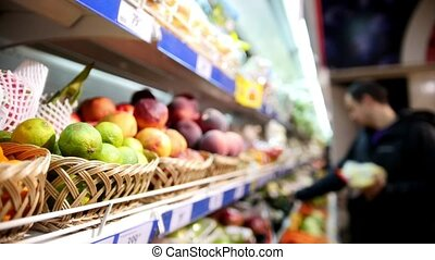 Customers choose products in grocery shelf with fruit an vegetables in supermarket