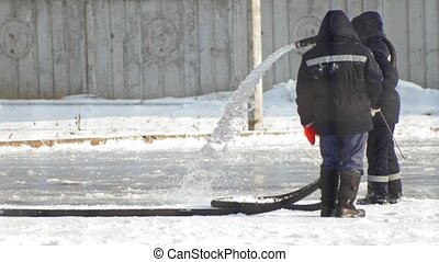 Making ice skating - two man pouring water from a hose and creates an ice skating rink, close up