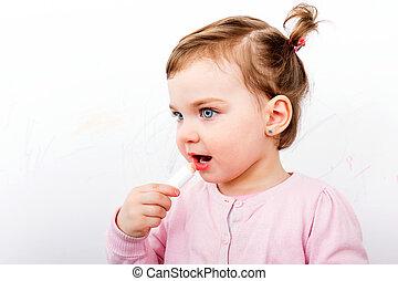 Adorable sweet child - Adorable sweet girl applying lip balm...