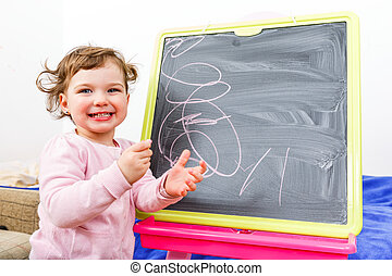 Little girl drawing on blackboard - Cheerful beautiful...