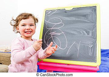 Little girl drawing on blackboard - Cheerful beautiful...
