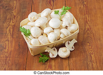 Cultivated button mushrooms in the wooden basket and near her