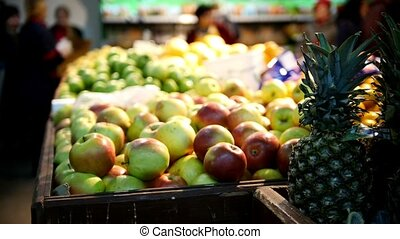 Supermarket - pineapple, green and red apples in fruit...