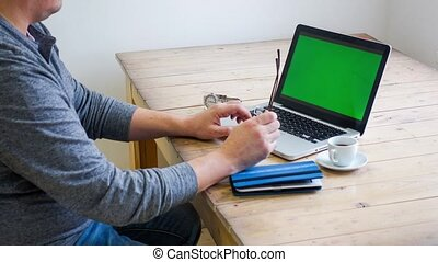 Man working at a laptop on a wooden table. Screen filled by...