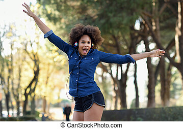 Young black woman with afro hairstyle jumping in urban...
