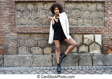 Young black woman with afro hairstyle standing in urban...
