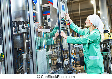 worker operating conveyor or labeling machine at factory -...