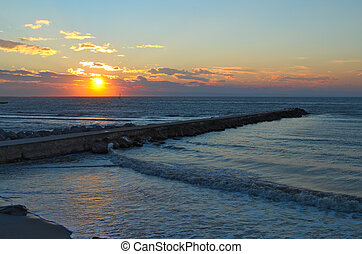 Sunrise on the sea with a breakwater made of rocks entering in the sea