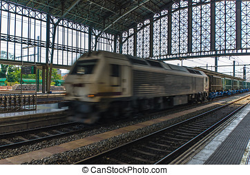 goods train speeding through train station - A freight train...