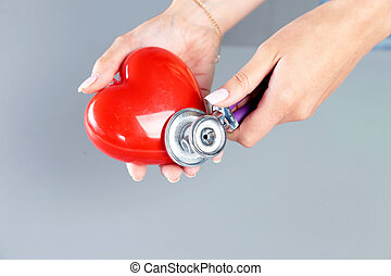 Female medicine doctor hold in hands red toy heart and stethoscope head. Cardio therapeutist, student education, physician make cardiac physical, rate measure, arrhythmia concept