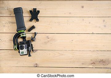 Action camera on the wooden table with a stabilizer and...