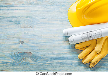 Hard hat rolled construction drawings protective gloves on...