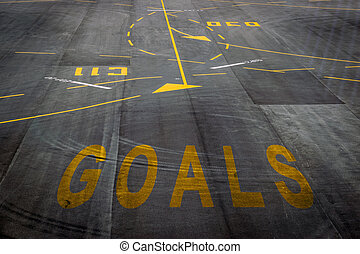 The goals words on the surface of the airport runway...