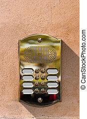 Golden Intercom on a Wall - Detail of a golden intercom with...
