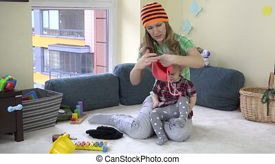 Mother with cute baby girl measure colorful knitted hats between toys