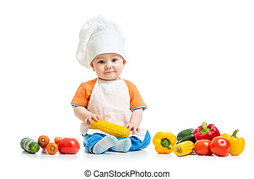 Smiling chef kid boy with vegetables isolated on white...