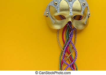 Maris gras mask and beads on yellow background with copy...