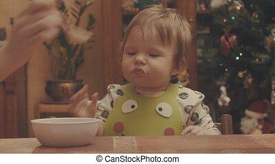 Someone feeding the baby porridge, then she takes the spoon...