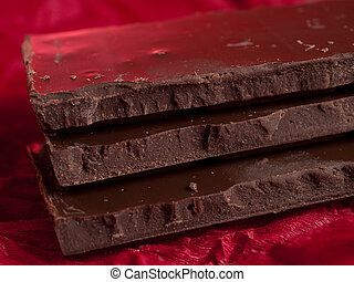 Dark chocolate - Three pieces of dark chocolate on red...