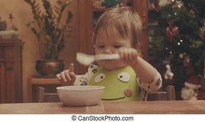 Baby playing with the spoon and eating porridge. Eye level...