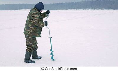 Winter fishing on river. A man drills a hole in ice.