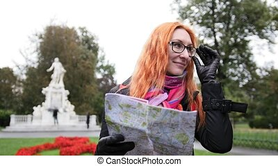 Yong woman tourist with red hair adjusts her glasses and...