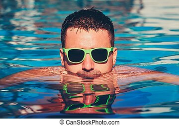 Sunny day in the pool - Young man with sunglasses resting in...