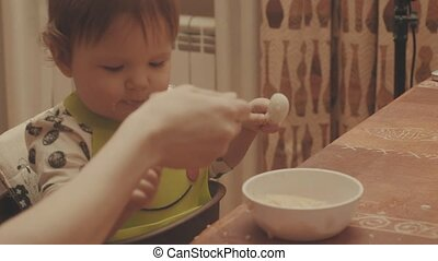 Baby playing with the spoon and eating porridge. Close up,...