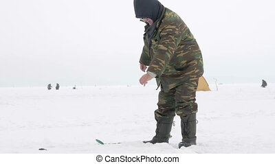 The man is engaged in winter fishing. It costs about fishing...