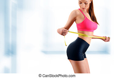 Young woman measuring herself. Weight loss.