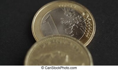 Pound Coins and Euro coins with macro shot, brexit concept,...