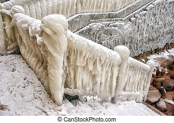 ice covered staircase on the beach on cold gloomy winter day...