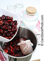 Cherry jam making - Adding cherries to the cooking pot, with...