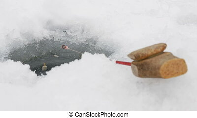 Fishing rod for winter fishing near the hole in the ice. The float moves through the water