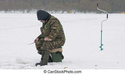 The man is engaged in winter fishing. It costs about fishing rods waiting fish. Warmly dressed in protective clothing