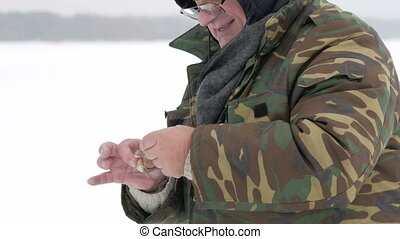 The man caught a small fish on ice fishing. He takes it off...