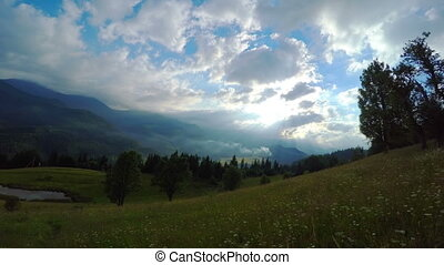 Sun Rays Pass through the Clouds Over the Mountains at...