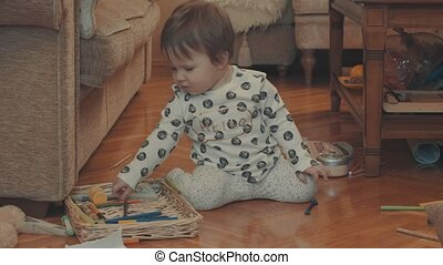 Little baby playing with a color pencils, then crawling on the drawing