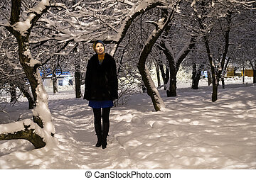 Portrait of woman in a winter park - Smiling woman in a fur...