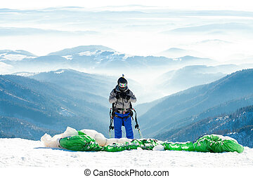 Paraglider in helmet preparing to get launched from snowy...
