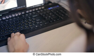 Black keybord in front of monitor with one woman hand. There...