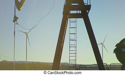 Pumpjack extracting petroleum on an oil well with Wind power...