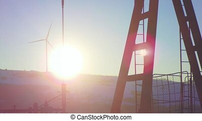 Sunshine on an oil well with pumpjack and Wind power plant in background