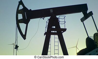 Pumpjack extracting petroleum on an oil well with Wind power plant in background