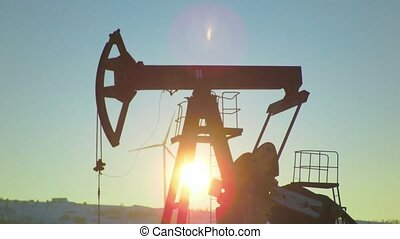 Sunshine on an oil well with pumpjack and Wind power plant...