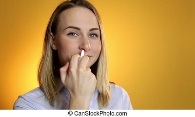 Woman using medical nasal spray for her nose.