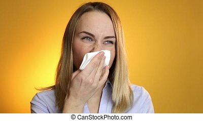 Sick woman blowing his nose into tissue on a yellow...